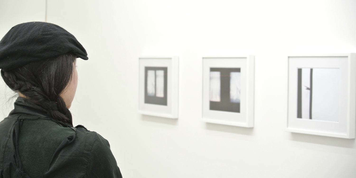 Photographer Maiko Haruki in front of her work