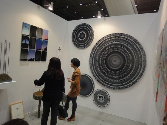 Booth of Island gallery. The black paintings on the back looks like annual growth rings.