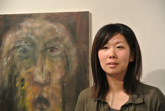 Akiko Kinugawa standing next to her work.