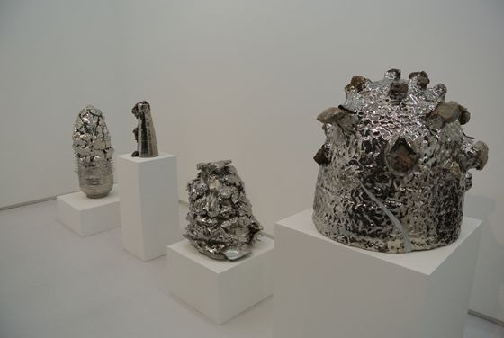 Four bigger and distinguished art pieces completely covered in silver metallic color