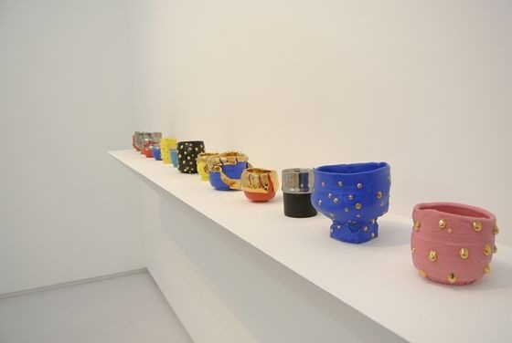 Tea cups by Takuro Kuwata lined in the exhibition space.