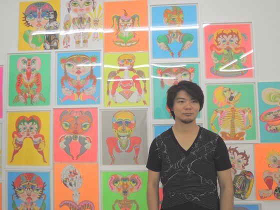 Mr. Nanzuka in front of Keiichi Tamaami's drawings