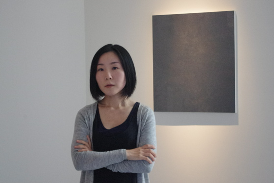 "Naoko Sekine standing in front of ""The captured charm"" 2012"