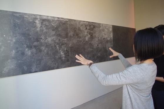"The artist explaining her three-piece work, ""The sound before the words, the voice of the puppeteer, one space: The sense of separation"" 2012"