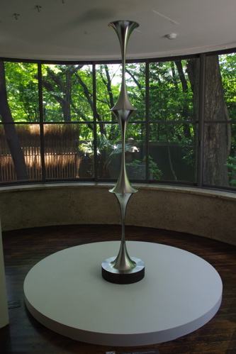 """Fixed Ration Negative Curvature Hyperbolic Rotational Plane"" by Hiroshi Sugimoto (2012) in the sunroom, with a partial view of ""Art Brooms (Kaerinagaki)"" (2012) outside."