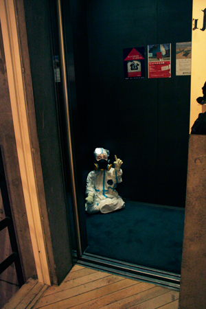 A figure wrapped in a hazmat suit set in the Museum elevator